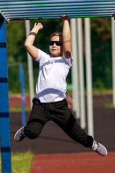 Um menino loiro de óculos escuros exercícios em um campo de esportes. foto de alta qualidade
