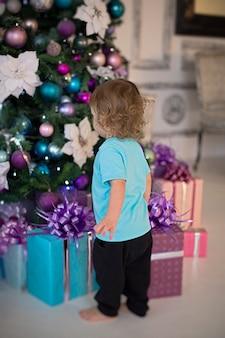 Um menino loiro encaracolado com uma camiseta cor de menta olha para os presentes sob a árvore de natal