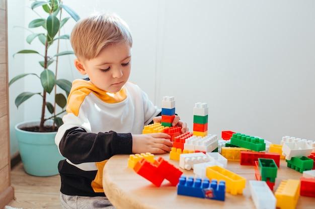 Um menino loiro está brincando com um kit de construção, com uma parede de madeira ao fundo. conceito de jogos educativos