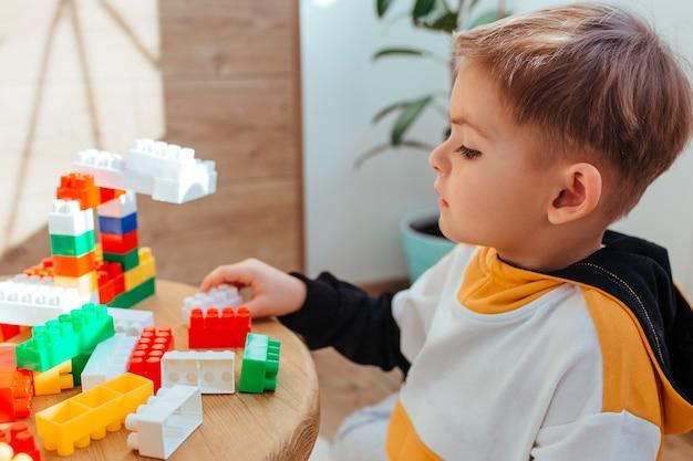 Um menino loiro está brincando com um kit de construção, com uma parede de madeira ao fundo. fechar-se