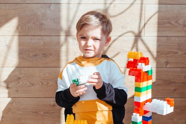 Um menino loiro está brincando com um kit de construção, com uma parede de madeira ao fundo