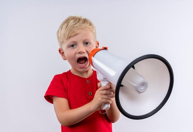 Um menino loiro fofo vestindo uma camiseta vermelha falando no megafone enquanto olha para uma parede branca