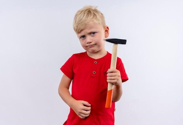 Um menino loiro sério e fofo com uma camiseta vermelha segurando um martelo enquanto olha para uma parede branca