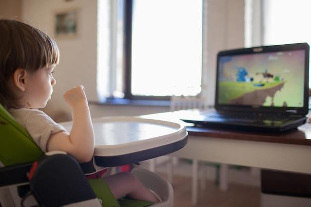 Um menino louro pequeno que olha desenhos animados.