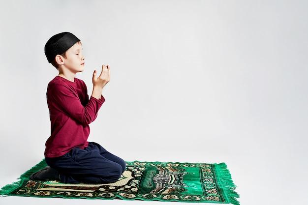 Um menino muçulmano faz uma oração no feriado do ramadã