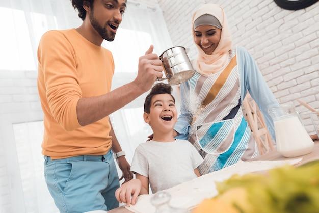 Um menino na cozinha com sua família.