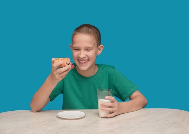 Um menino na mesa com uma camiseta verde bebe leite e come uma torta.