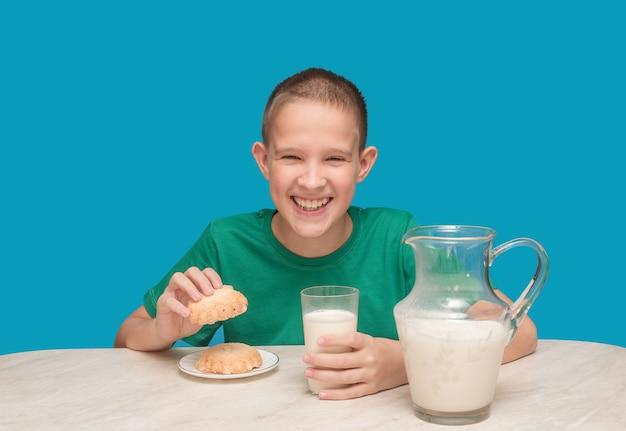 Um menino na mesa da cozinha com uma camiseta verde bebe leite e come biscoitos.