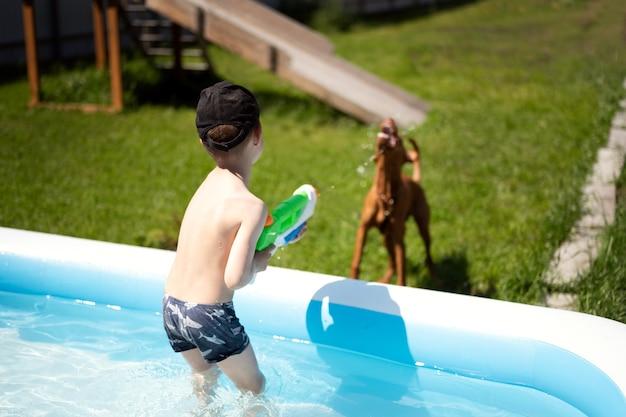 Um menino na piscina está brincando com uma pistola d'água atira um jato d'água no cachorro que o cachorro pega