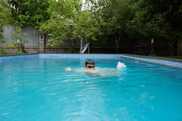 Um menino nada no verão na piscina do quintal.
