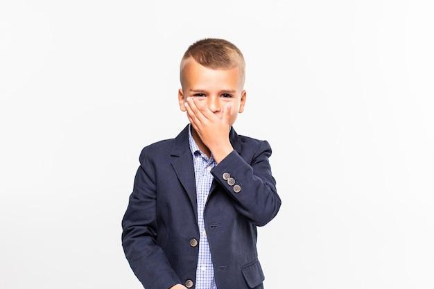Um menino novo assustado chocado que cobre sua boca com sua mão isolada no branco.
