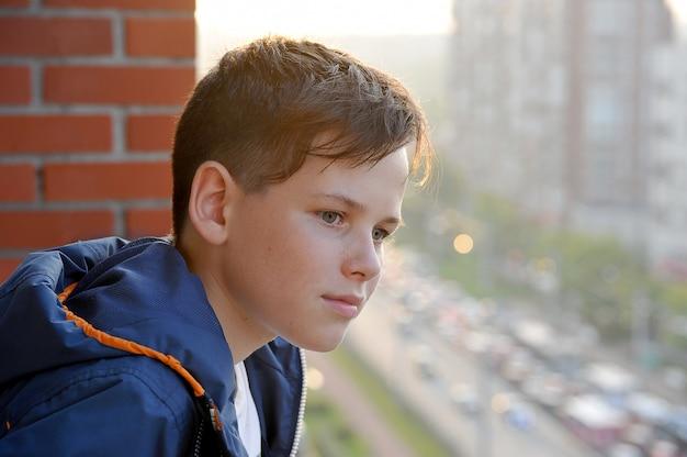 Um menino olha da varanda