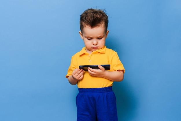 Um menino olha para a tela de um telefone celular.