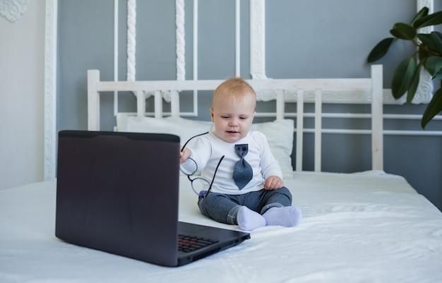 Um menino pensativo de terno está sentado na cama com um laptop