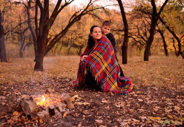 Um menino pequeno com sua mãe coberto com um cobertor xadrez sentado perto do fogo no fundo da floresta de outono