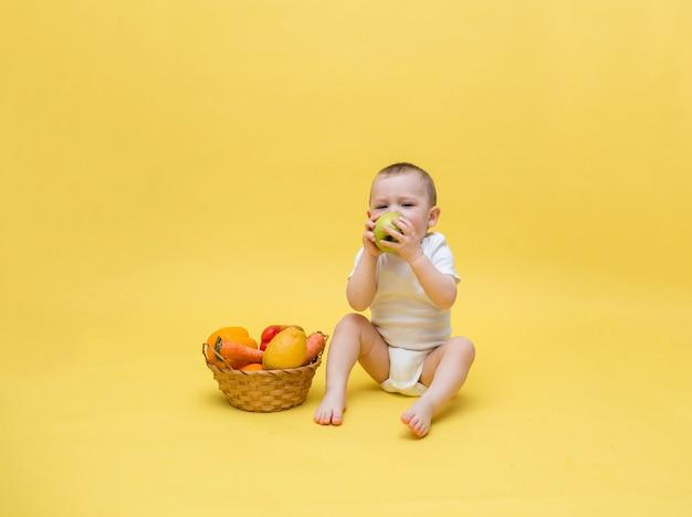Um menino pequeno com uma cesta de vime com legumes e frutas em um espaço amarelo. o garoto está sentado em uma roupa branca e comendo uma maçã. espaço livre em um espaço amarelo.
