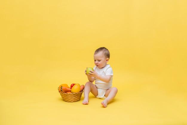 Um menino pequeno com uma cesta de vime com legumes e frutas em um espaço amarelo. o garoto está sentado em uma roupa branca e comendo uma maçã. olhando para o lado.