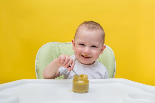 Um menino pequeno come purê de brócolis por conta própria em uma cadeira alta em um amarelo isolado