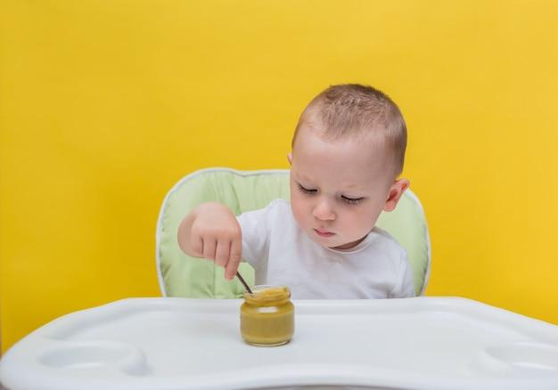Um menino pequeno come uma colher de brócolis em uma mesa em um amarelo isolado