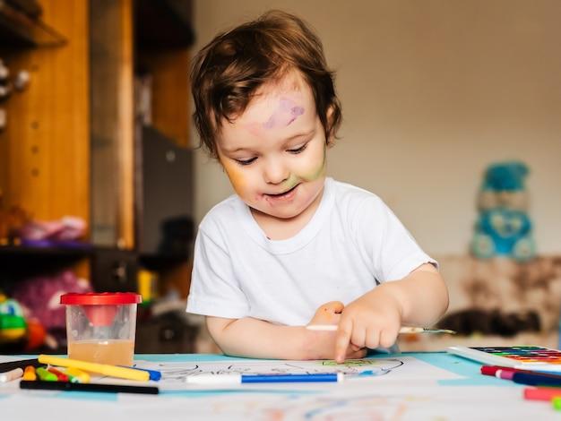Um menino pequeno e bonito pinta com pincéis e tintas coloridas em uma folha de papel