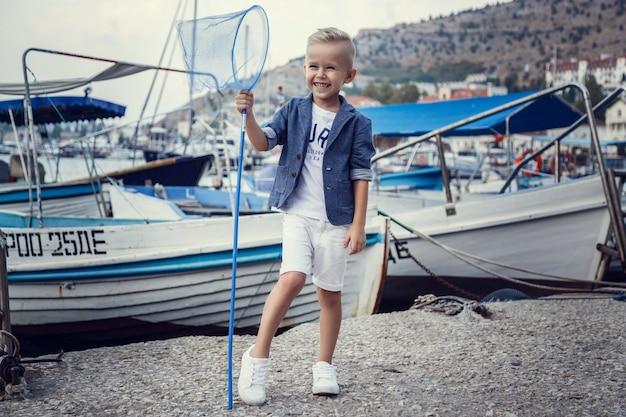 Um menino pequeno em estilo marinho, no contexto de barcos e iates. ideia e conceito amizade, férias, férias, família