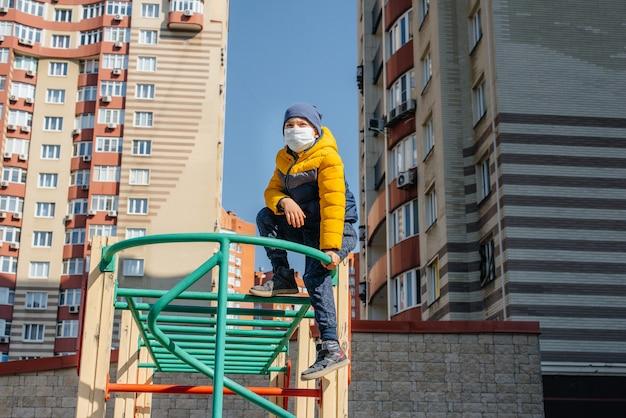 Um menino pequeno em uma máscara caminha no recreio durante a quarentena. ficar em casa