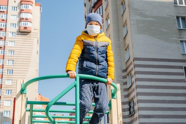 Um menino pequeno em uma máscara caminha no recreio durante a quarentena. ficar em casa.
