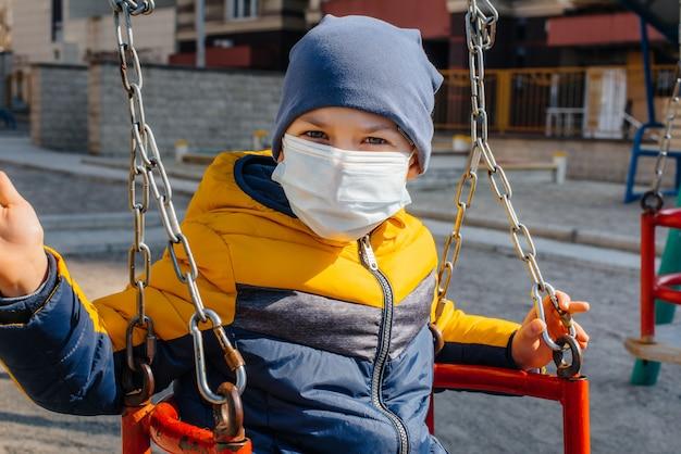 Um menino pequeno em uma máscara caminha no recreio durante a quarentena.
