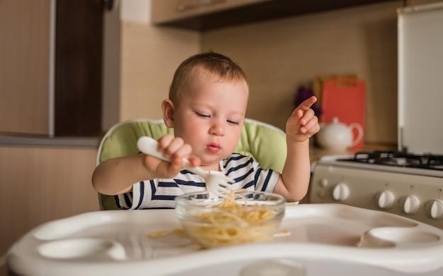 Um menino pequeno se senta em uma cadeira alta na cozinha e come macarrão sozinho.
