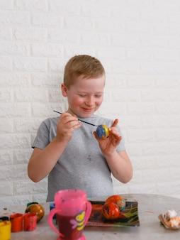 Um menino pinta ovos com tintas coloridas para celebrar o feriado da páscoa. conceito de férias Foto Premium