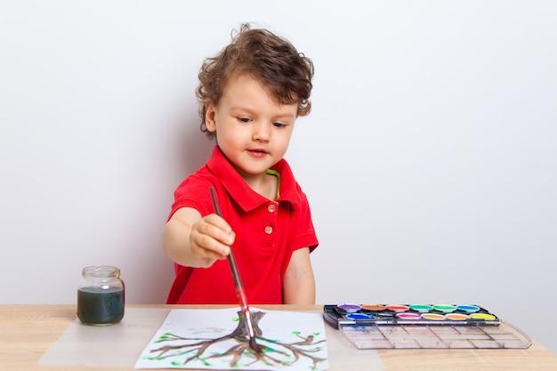 Um menino pinta uma árvore com folhas verdes com um pincel e pinta em uma folha de papel branca na mesa.