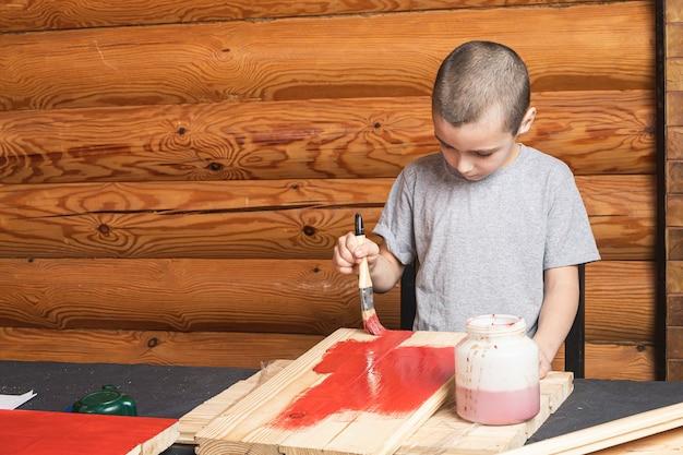 Um menino pinta uma falsa de madeira com um pincel de vermelho em uma casa de campo