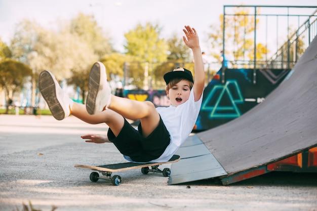 Um menino pratica manobras em um skate em uma área especial do parque.