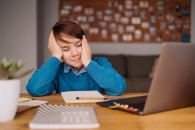 Um menino pré-adolescente farto de aulas online