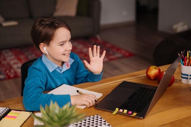 Um menino pré-adolescente usa um laptop para dar aulas on-line e diz olá para a professora