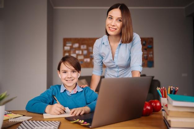 Um menino pré-adolescente usa um laptop para fazer uma videochamada com a professora ao lado da mãe