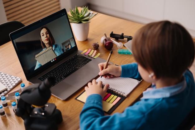 Um menino pré-adolescente usa um laptop para fazer uma videochamada com a professora