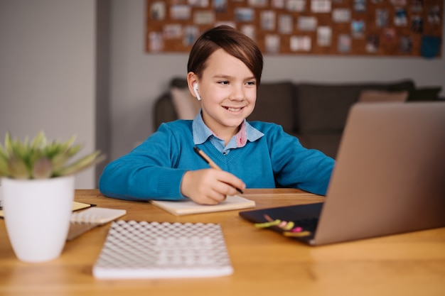 Um menino pré-adolescente usa um laptop para fazer uma videochamada com o professor, aulas online, fazer anotações
