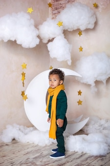 Um menino preto de suéter verde e cachecol amarelo custa cerca de um mês, pensativo. um pequeno príncipe. pouco americano africano. criança pensativa. a criança se diverte e brinca no jardim de infância. escola