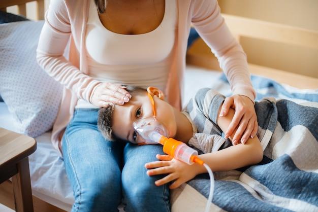 Um menino recebe uma inalação de sua mãe durante uma doença pulmonar. medicina e cuidados.