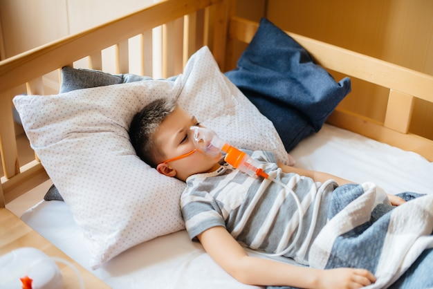 Um menino recebe uma inalação durante uma doença pulmonar. medicina e cuidados.