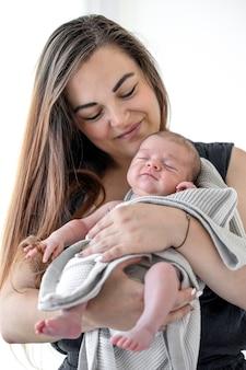 Um menino recém-nascido dorme docemente nos braços de sua mãe, envolto em um cobertor.