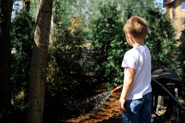 Um menino regando plantas e árvores de natal decorativas no quintal de sua casa.