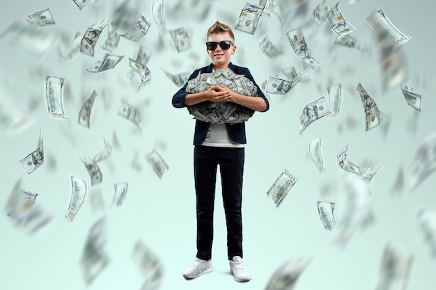 Um menino rico e fofo com óculos tem dólares e sabe como ganhar dinheiro no contexto da queda das notas. chuva de dinheiro, educação financeira, jovem milionário, investimentos, empréstimos, ganhos