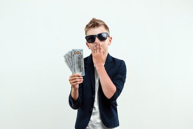 Um menino rico em um fundo claro tem um pacote de dólares nas mãos. educação financeira.