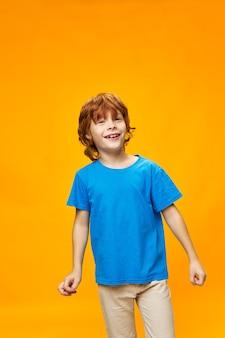 Um menino ruivo com uma camiseta azul e um fundo amarelo sorri