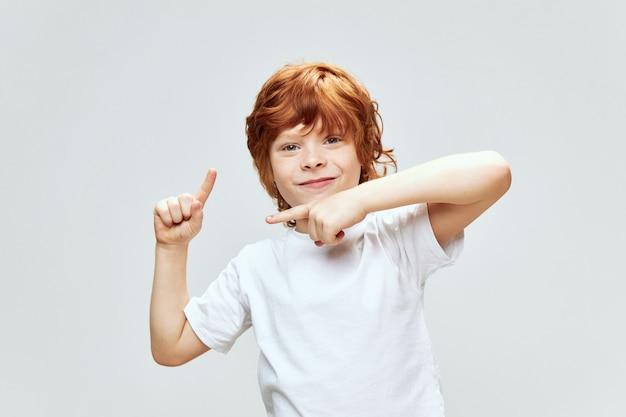 Um menino ruivo gesticula com os dedos em uma camiseta branca