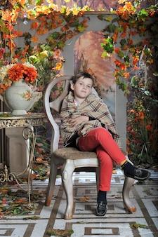 Um menino se senta em uma cadeira com um cobertor