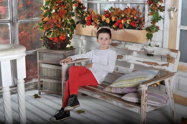 Um menino se senta em uma cadeira no jardim no outono