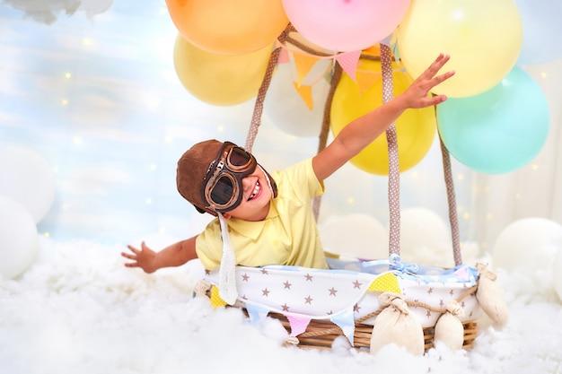 Um menino senta-se em uma cesta de balão nas nuvens